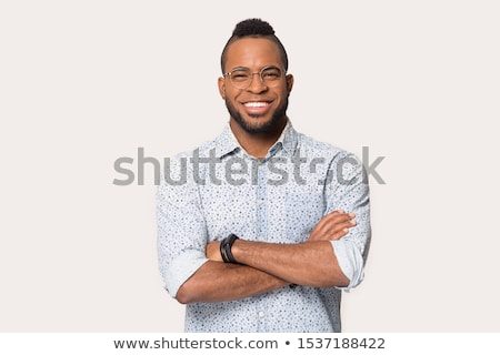 Image of young bearded handsome man wearing eyeglasses smiling at camera Stock photo © deandrobot