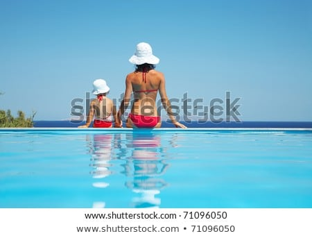 Little girl relaxing in swimming pool, enjoying suntans, swims on inflatable yellow mattres Stock photo © Illia