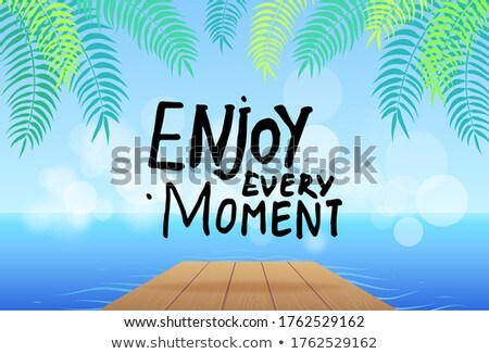 Enjoy every moment slogan at background of sea, wooden bridge, green leaves of exotic plant Stock photo © robuart