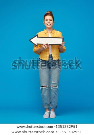 red haired teenage girl with arrow showing to left Stock photo © dolgachov