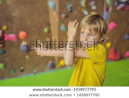 The boy is warming up before climbing a rock wall indoor Stock photo © galitskaya