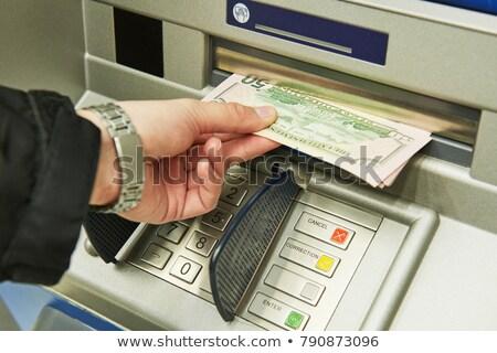hand inserting banknote into cash dispense Stock photo © Mikko
