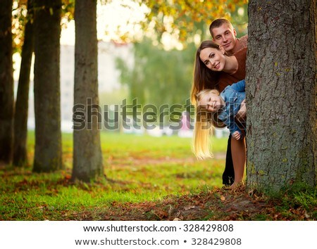 Stock photo: Couple standing behind a tree trunk