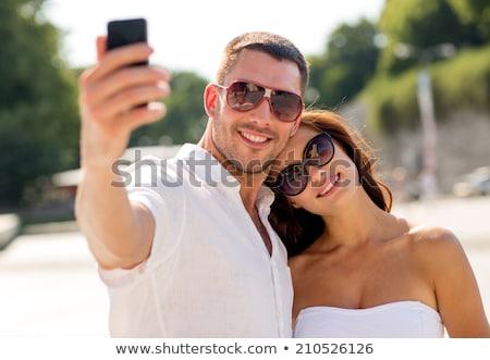 smiling couple wearing sunglasses making selfie Stock photo © dolgachov