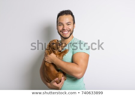 Young attractive mexican man at home with teckel dog Stock photo © Lopolo