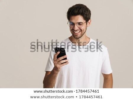 Image of young unshaven man posing and using cellphone Stock photo © deandrobot