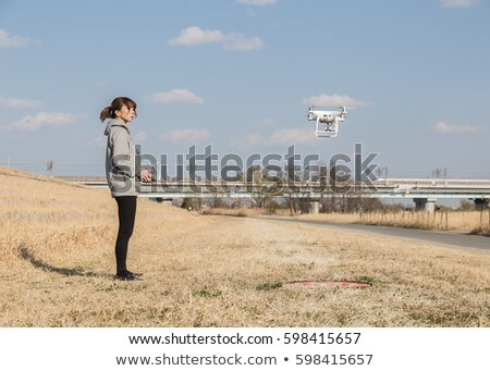 Pretty. young female flying a drone outdoors Stock photo © lightpoet