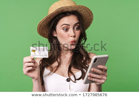 Image of amusing caucasian woman holding cellphone and credit card Stock photo © deandrobot