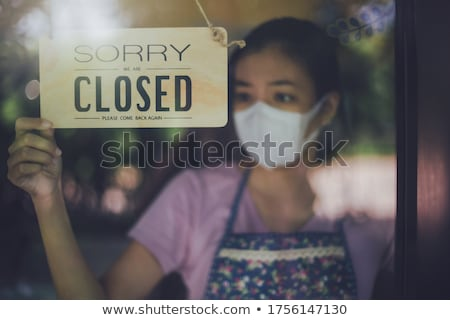 Sad Female Store Owner Turning Sign to Closed in Window Stock photo © feverpitch
