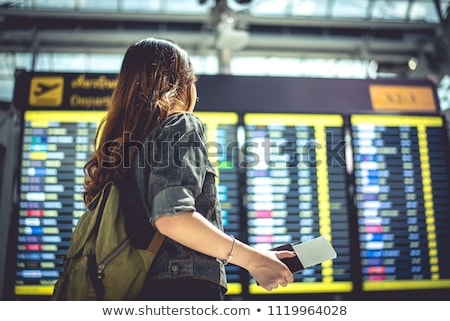 Travel airport tourist woman waiting for delayed flight looking at airport terminal screens showing  Stock photo © Maridav