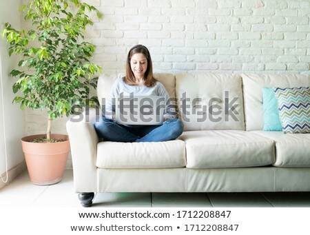 Smiling woman sitting on couch Stock photo © IS2
