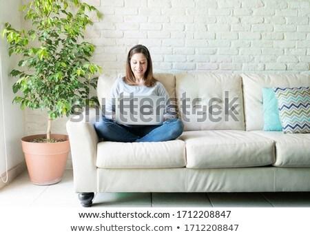 улыбающаяся женщина сидят диване женщину весело диван Сток-фото © IS2