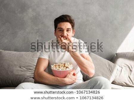 éhes kaukázusi férfi 20-as évek ül kanapé Stock fotó © deandrobot