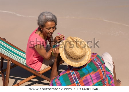High angle view of senior couple relaxing on sun lounger and drinking cocktail on the beach in sunsh Stock photo © wavebreak_media