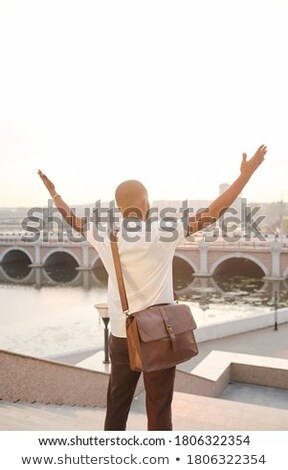 Rear view of Caucasian businessman raising hand while he is sitting in front of Asian businessman at Stock photo © wavebreak_media