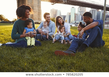 Front view of multi ethnic group of friends relaxing and sitting on beach while looking at camera Stock photo © wavebreak_media