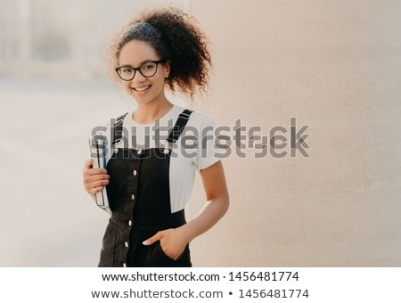 Lovely curly woman with combed hair, dressed in white t shirt, sarafan, keeps hand in pocket, holds  Stock photo © vkstudio