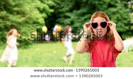 naughty red haired girl in heart shaped sunglasses Stock photo © dolgachov