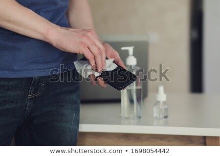 Cleaning mobile phone screen with disinfecting wet wipes for clean smartphone preventive wiping for  Stock photo © Maridav