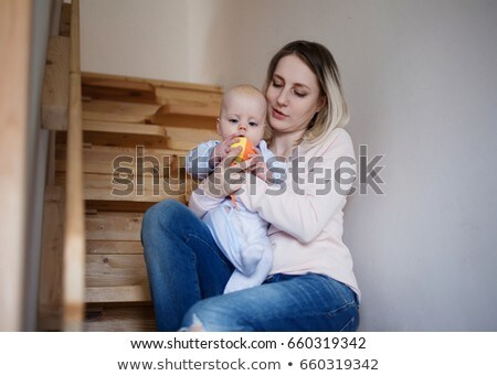 Young mother with a child sitting on the stairs, house Stock photo © Lopolo