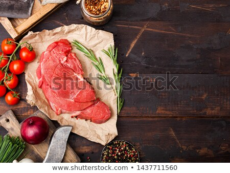 Fresh raw organic slice of braising steak fillet on butchers paper with fork and knife on dark woode stock photo © DenisMArt