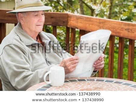 senior man reading newspaper outdoors at home stock photo © highwaystarz
