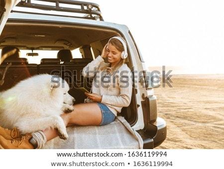 Woman with dog samoyed using mobile phone. Stock photo © deandrobot