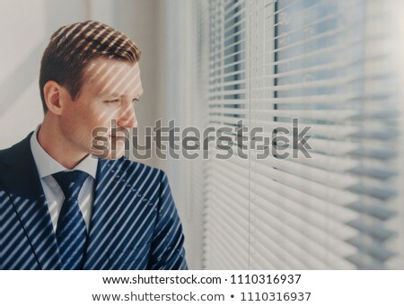 Indoor shot of pensive male economist dressed in formal outfit, looks pensively at window with jalou Stock photo © vkstudio