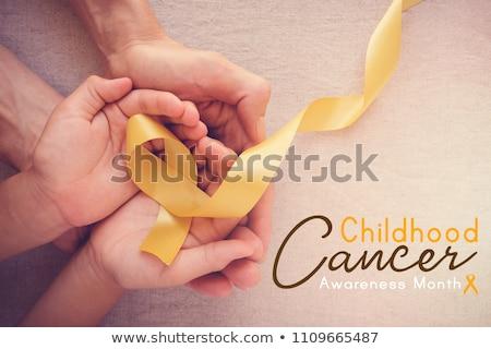 Ręce żółty złota raka świadomość Zdjęcia stock © dolgachov