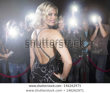 Beautiful young woman standing on a red carpet Stock photo © Nejron