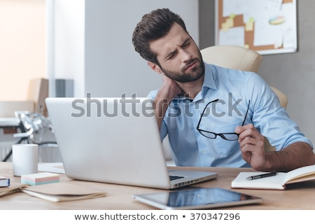 business man holding one hand to his neck stock photo © feedough