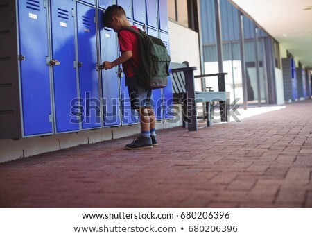 Sad boy leaning on locker Stock photo © wavebreak_media