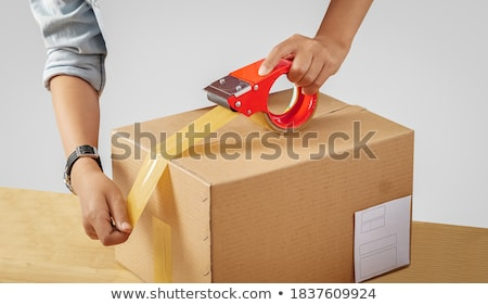 warehouse worker packing parcel with scotch tape Stock photo © dolgachov