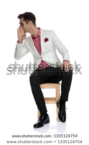young elegant man chitchats gissip to his side while sitting Stock photo © feedough