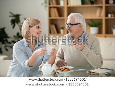 Cheerful young woman and her elderly father with tea looking at each other Stock photo © pressmaster