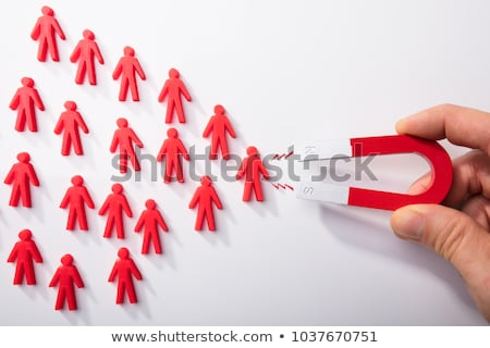 Human Hand Attracting Human Figures With Horseshoe Magnet Stock photo © AndreyPopov