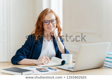 Successful economist in eyewear, checks information on laptop computer, reads information on financi Stock photo © vkstudio