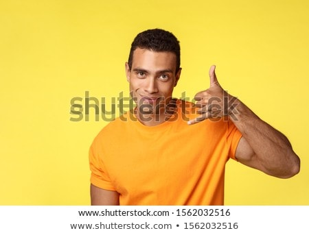 Cheeky and sassy handsome young brazilian man trying seduce woman, make phone gesture near ear and s Stock photo © benzoix