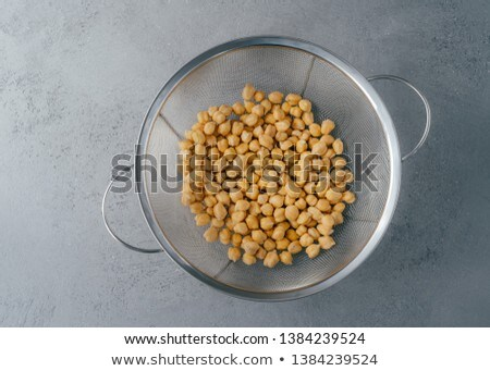 Overhead view of chickpeas in sieve against grey background. Legumes for vegans. Organic dish. Healt Stock photo © vkstudio