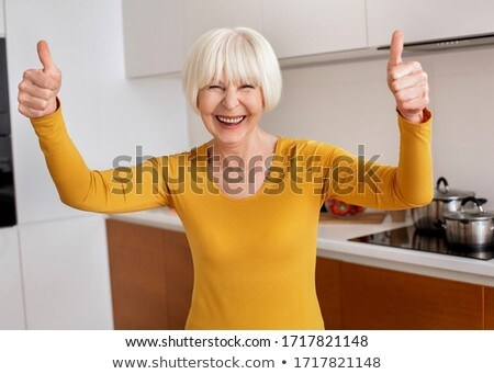 smiling senior woman showing thumbs up in kitchen Stock photo © dolgachov