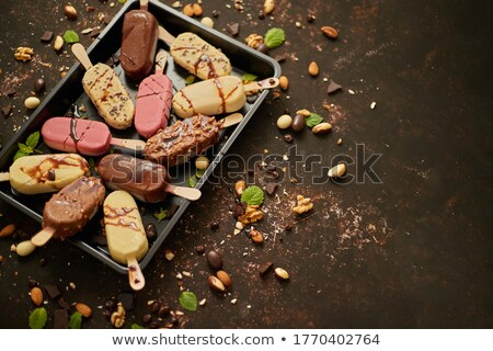 Ice cream on stick coated with various chocolate glazes and toppings. Top view, flat lay Stock photo © dash