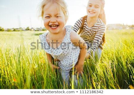 Girl at green grass field at sunset. Stock photo © Massonforstock