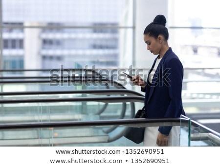 Yandan görünüş güzel genç işadamı cep telefonu yürüyen merdiven Stok fotoğraf © wavebreak_media