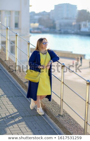 A woman in sunglasses walks along the waterfront after city shopping on a tourist trip Stock photo © ElenaBatkova