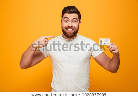 handsome young bearded man holding credit card pointing stock photo © deandrobot