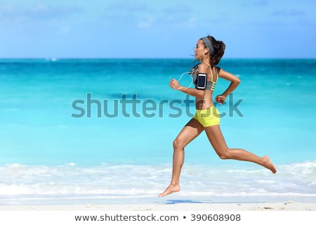 woman with earphones and armband running on beach Stock photo © dolgachov