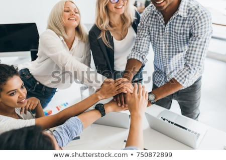 Image of multiethnic young coworkers working on laptops in offic Stock photo © deandrobot