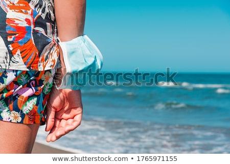 Homem máscara cirúrgica braço praia Foto stock © nito