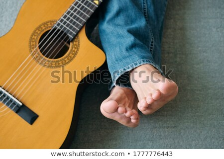 Barefoot Guitarist With Legs Outstretch Beside Guitar Stock photo © diego_cervo