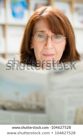 Elderly woman with glasses reading newspaper in library stock photo © diego_cervo